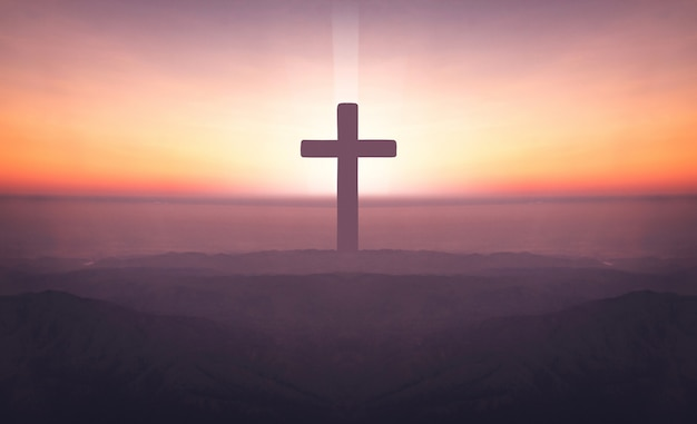 Silhouette of crucifix cross on mountain at sunset time with holy and light background. Premium Photo