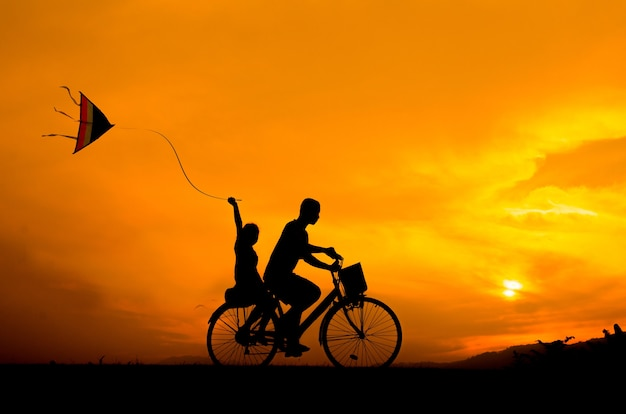 Silhouette cycling brother and sister with kite. Premium Photo