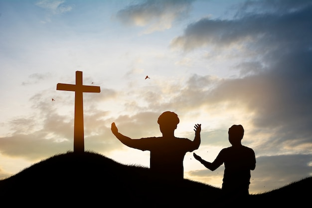 Silhouette family looking for the cross of jesus christ on autumn sunrise Premium Photo