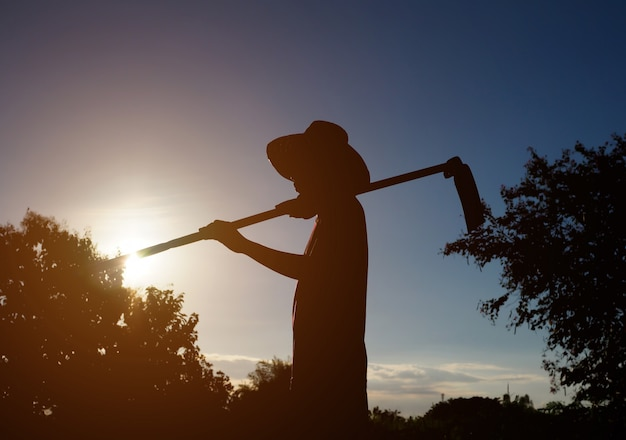 Silhouette of a farmer with sunset in nature landscape Premium Photo