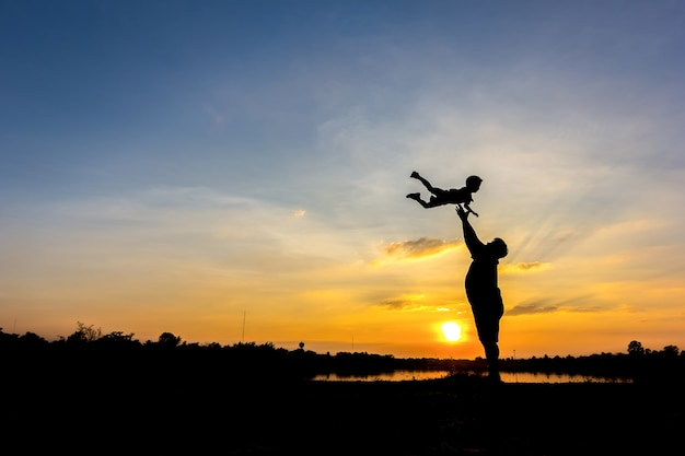 Silhouette of father throwing son into the sky. , father and son in sunset background Free Photo