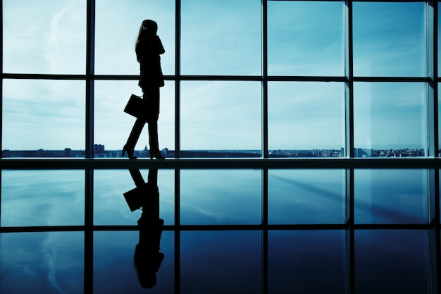 Silhouette of female executive with briefcase Free Photo