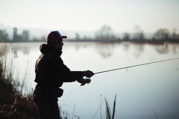 Silhouette of a fisherman fishing on lake Free Photo