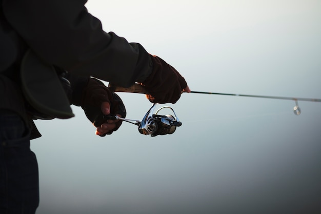 Silhouette of a fisherman's hand holding fishing rod Free Photo