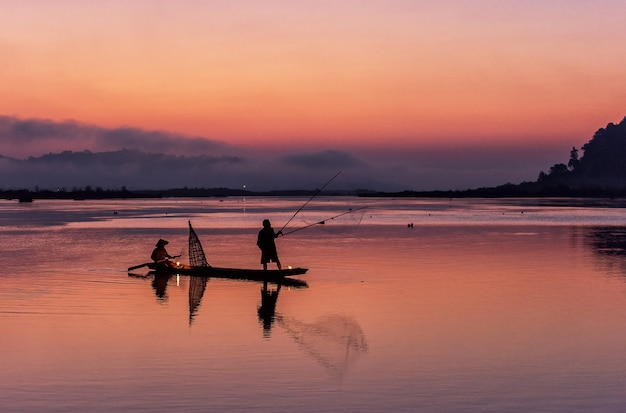 Silhouette of fisherman on wooden boat in nature lake with sunrise Premium Photo