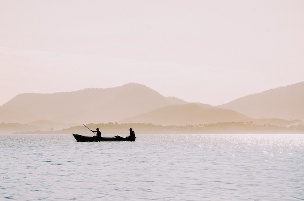 Silhouette of fishermen in a small boat Free Photo