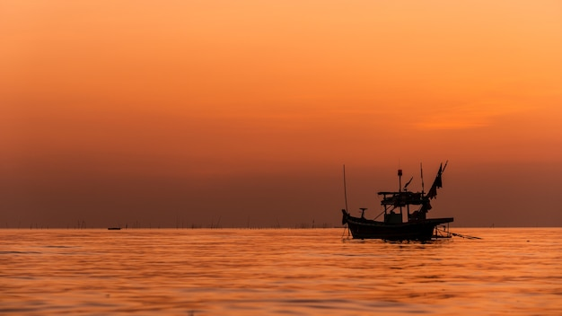 Silhouette of fishing boat with sunset in thailand. Premium Photo