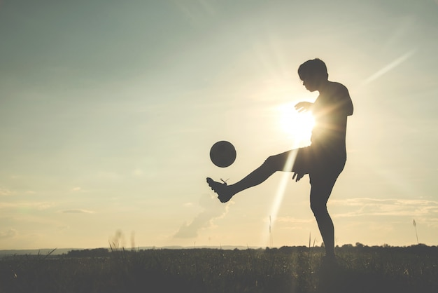 Silhouette of the football player with a soccerball against the sunset background. Premium Photo