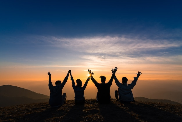 Silhouette of friends shake hands up and sitting together in sunset happiness Premium Photo