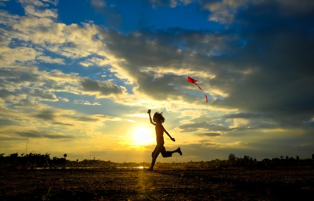 Silhouette of the girl flying a kite in sunset. Premium Photo