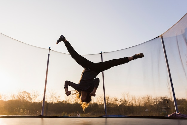 Silhouette of girl jumping on a trampoline doing split Free Photo