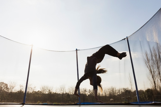 Silhouette of girl jumping upside down on trampoline against the blue sky Free Photo