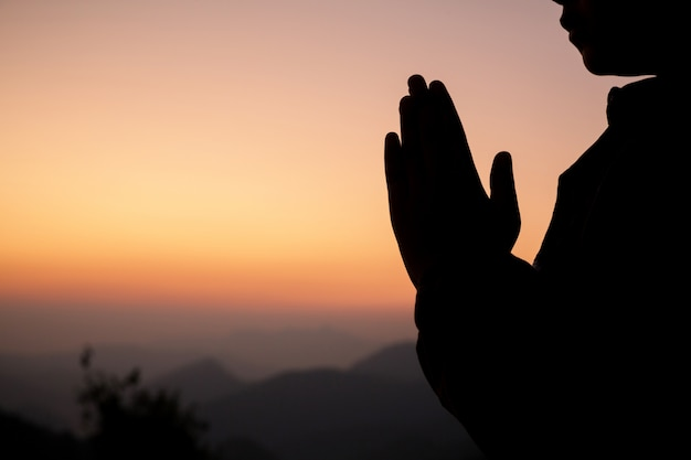 Silhouette of girl praying over beautiful sky background. Free Photo