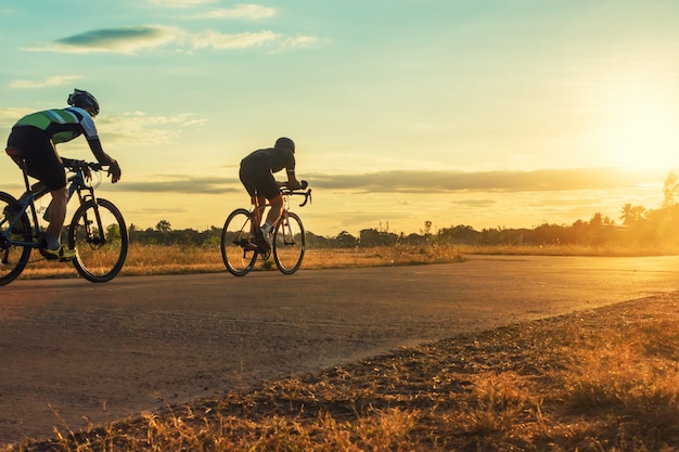 Silhouette group of men riding bicycle at sunset. Premium Photo