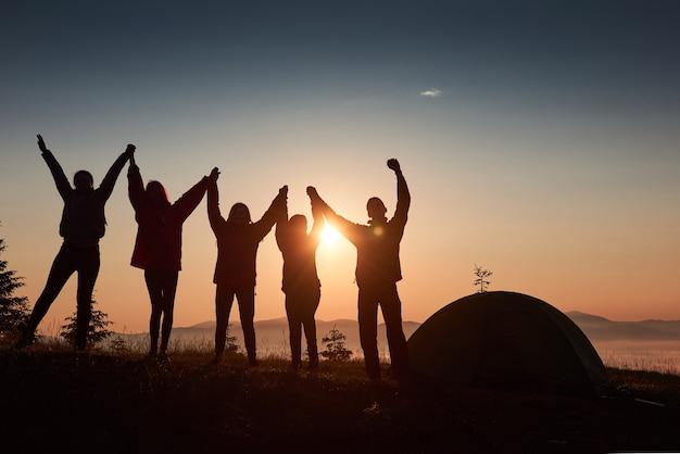 Una silhouette di persone di gruppo si diverte in cima alla montagna vicino alla tenda durante il tramonto. Foto Gratuite