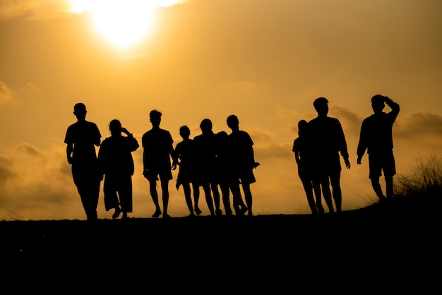The silhouette of a group of people is celebrating success on the hilltop. Premium Photo