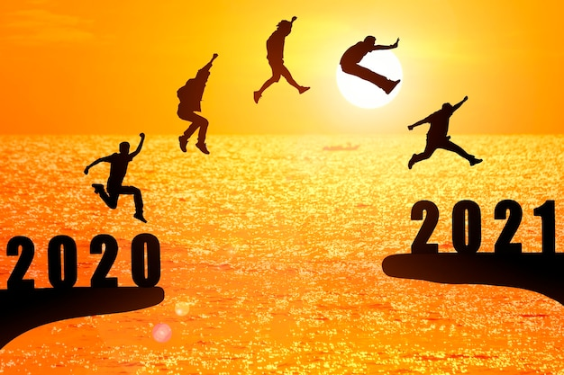 Silhouette group of young mans jumping between 2020 and 2021 years with beautiful sunset at the sea. Premium Photo