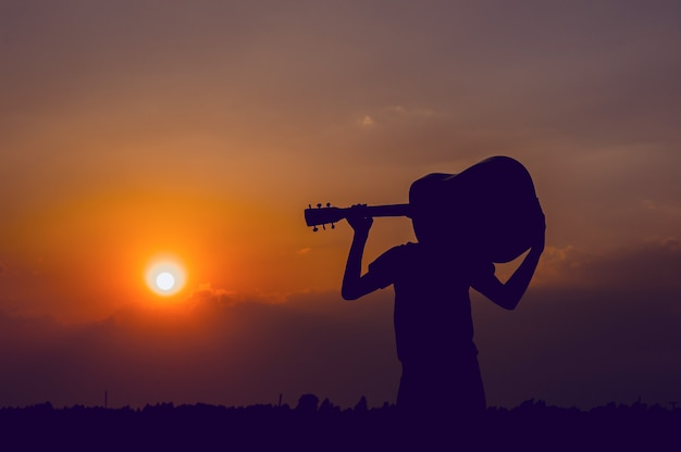 The silhouette of a guitarist who holds a guitar and has a sunset, silhouette concept. Premium Photo