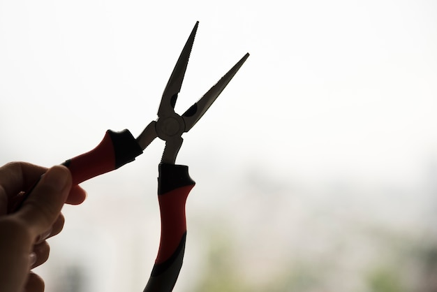 Silhouette of hand holding electric plier Free Photo