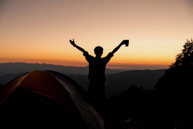 La siluetta dell'uomo felice con la tazza di caffè della tenuta resta vicino alla tenda intorno alle montagne Foto Gratuite