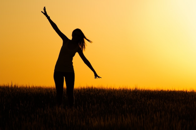 Silhouette of  happy young girl in field. Free Photo