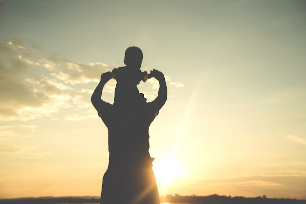 A silhouette of a happy young mother harmonious family outdoors. Premium Photo
