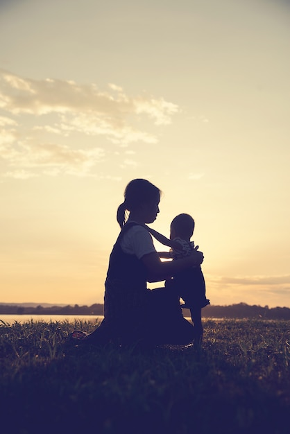 A silhouette of a happy young mother harmonious family outdoors Premium Photo