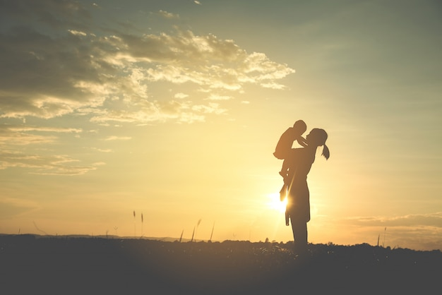 A silhouette of a happy young mother harmonious family in the summer Premium Photo