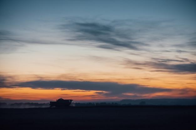 Silhouette of harvester machine to harvest wheat on sunset. Premium Photo