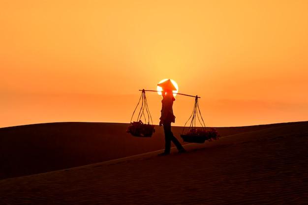 Silhouette of a hawker merchant traveling through the mui ne desert in vietnam Premium Photo