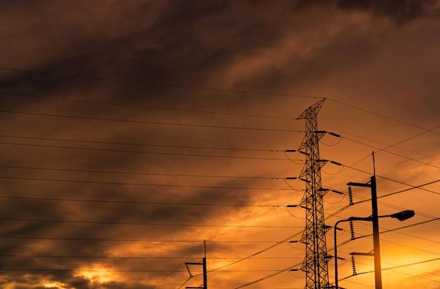 Silhouette высоковольтная электрическая опора и электрический провод с оранжевым небом. поляки электричества на заходе солнца. концепция власти и энергии. высоковольтная сеточная вышка с проводным кабелем. Premium Фотографии