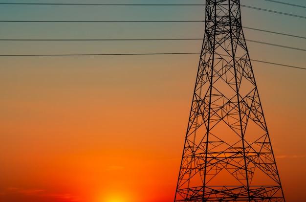 Силуэт высоковольтных электрических опор и электрических проводов с оранжевым небом Premium Фотографии
