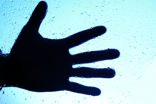 Silhouette of human hand over glass with drops Free Photo