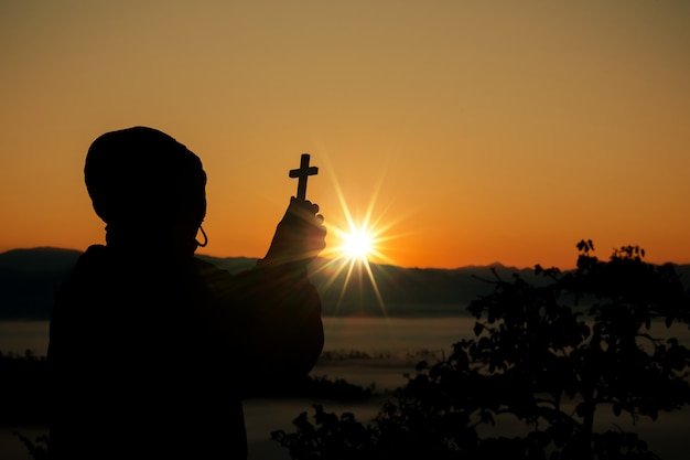 Silhouette of human hand holding the cross, the background is the sunrise Free Photo