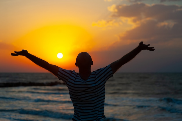 Silhouette image of man raising his hands with ray of light Premium Photo