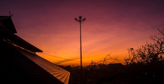 Silhouette image of sunrise on the roof Premium Photo