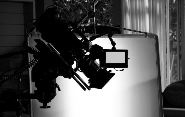 カメラマンとフィルムクルーチームがセットで操作または撮影し、プロのクレーンと三脚に支えて使いやすいテレビコマーシャルスタジオ制作のビデオカメラのシルエット画像 Premium写真