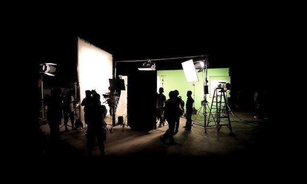 舞台裏でのビデオ制作、bロール、またはテレビコマーシャル映画の制作のシルエット画像。撮影クルーチームのライトマンとカメラマンがスタジオのディレクターと一緒に機器を使用して作業します。 Premium写真