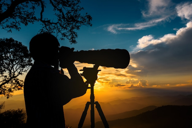 Silhouette of a landscape photographer use super telephoto lens at top of mountains during the sunset with two tone sunset sky Premium Photo