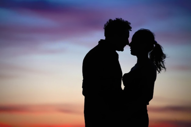 Silhouette of a loving couple against the sky after sunset Premium Photo
