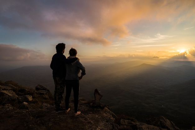 Silhouette of loving couple embracing on the mountain Premium Photo