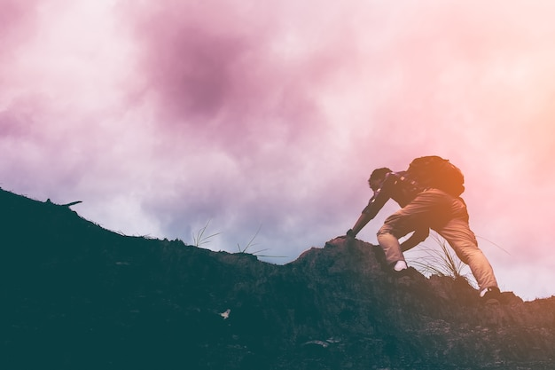 Silhouette of man climbing steep mountain. good image for adventure, struggle and success story photo. Premium Photo