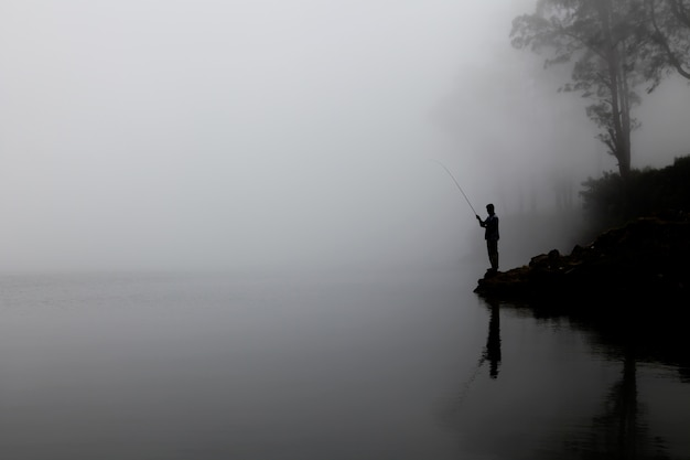 Silhouette of a man fishing on the lake with thick fog in the background Free Photo