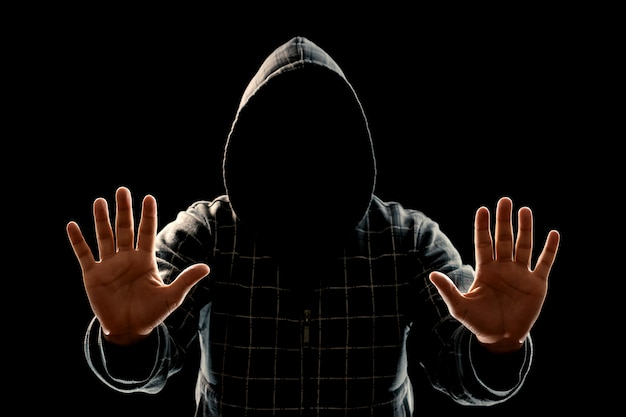 Silhouette of a man in a hood on a black background, the face is not visible, shows the palms in the camera. Premium Photo