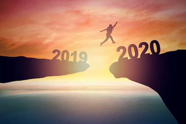 Silhouette of man jumping to 2020 Premium Photo