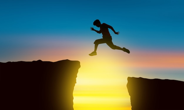 The silhouette of a man jumping over the abyss at the time of the sun set, concept of victory and success Premium Photo