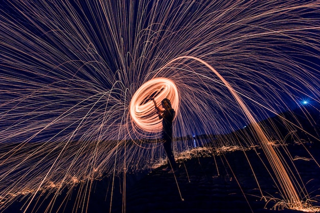 Silhouette of man making a circle of sparks at night Free Photo