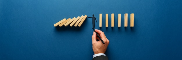 Silhouette of a man making a stop gesture to prevent wooden dominos from collapsing Premium Photo