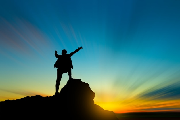 Silhouette of man on mountain top over sky and sun light ...