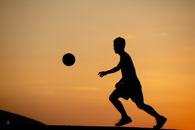 Silhouette of a man playing soccer in golden hour, sunset. Free Photo